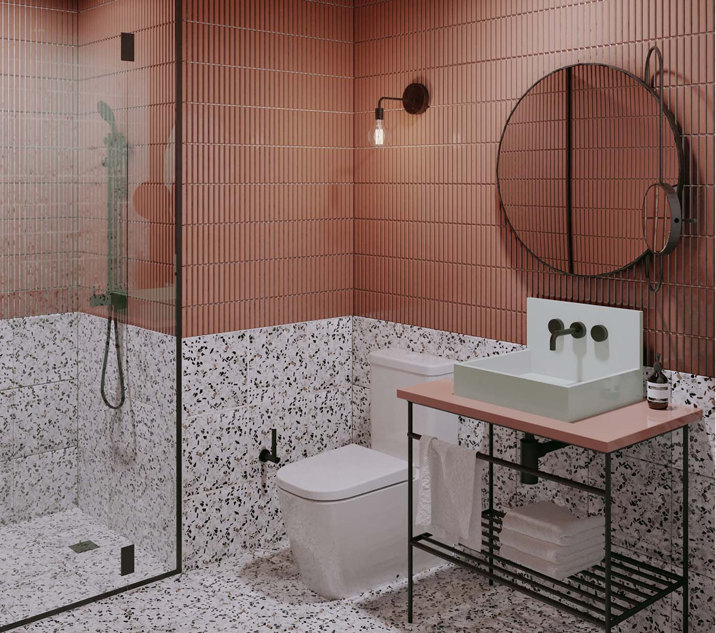 Hotel bathroom with pink and terrazzo tiles with round mirror.