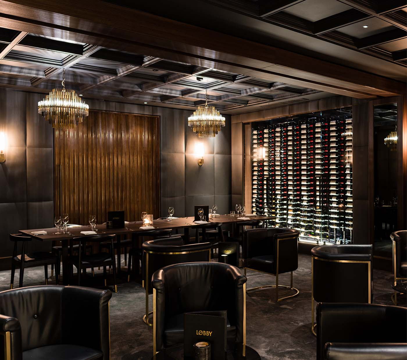 Restaurant room with dining tables and wine rack with dark colours.