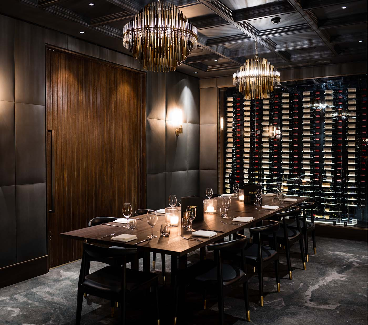Restaurant room with dining tables and wine rack with a dark palette.