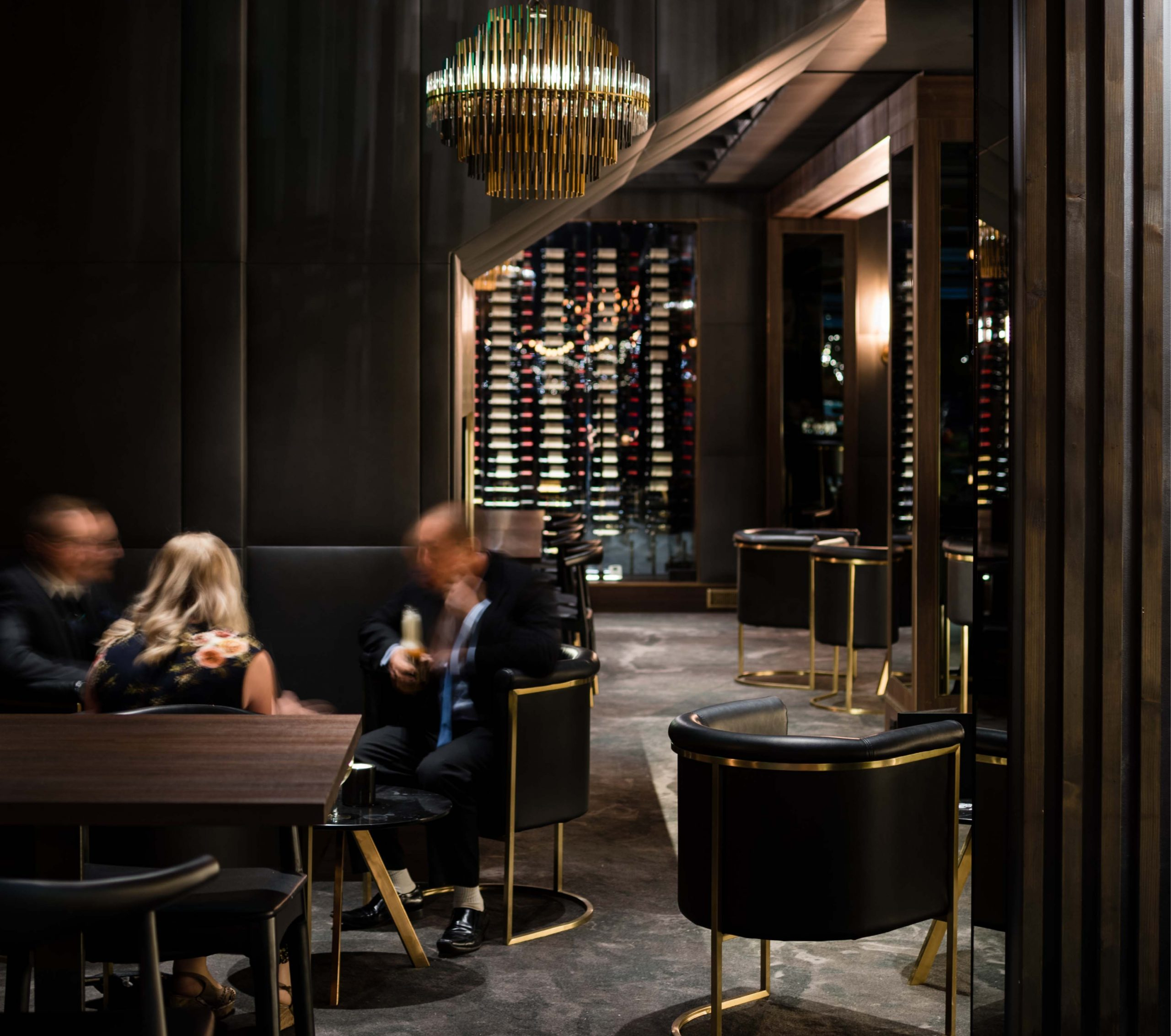 Restaurant room with dining table, people eating and wine rack with dark colours.
