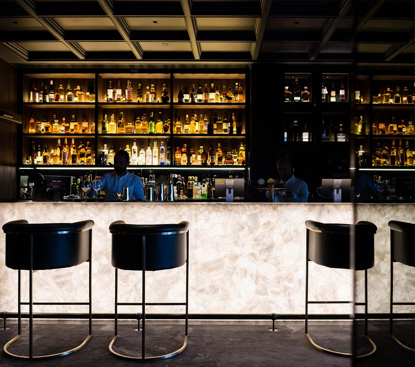 Whiskey bar detail with back-lit-onyx bar showing drinks and a man preparing cocktails.