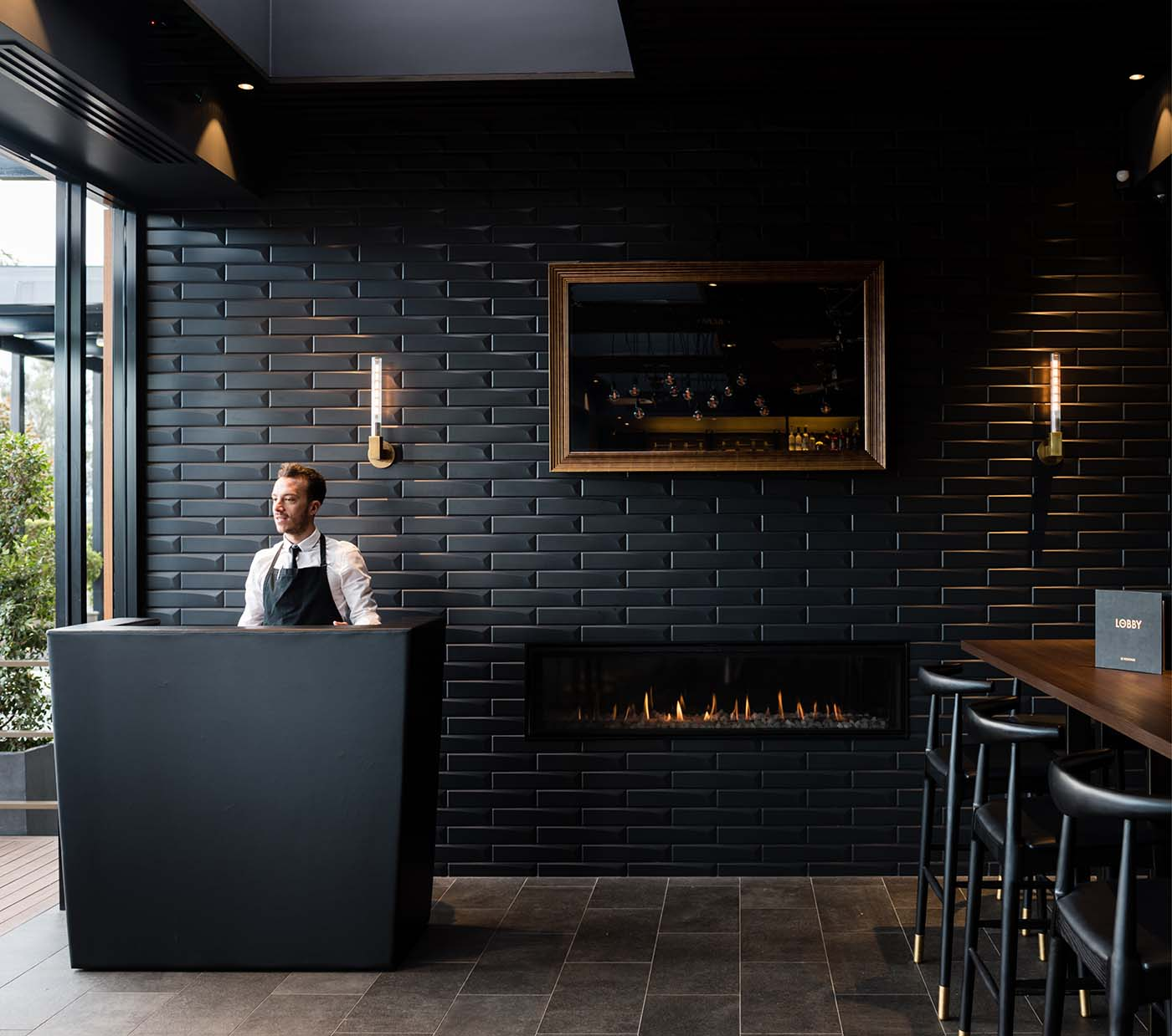 Receptionist in the reception of a whiskey bar with dark colours.