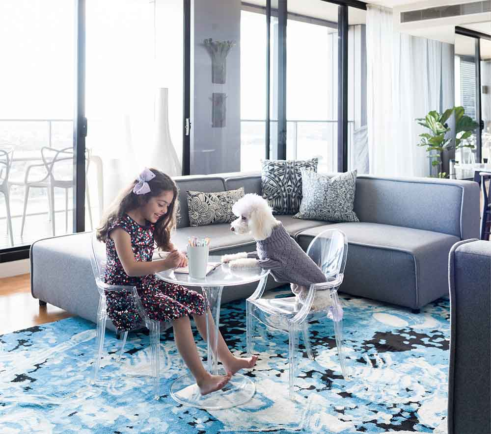 Living room close up with Lorena Gaxiola rug using a blue, white and black palette