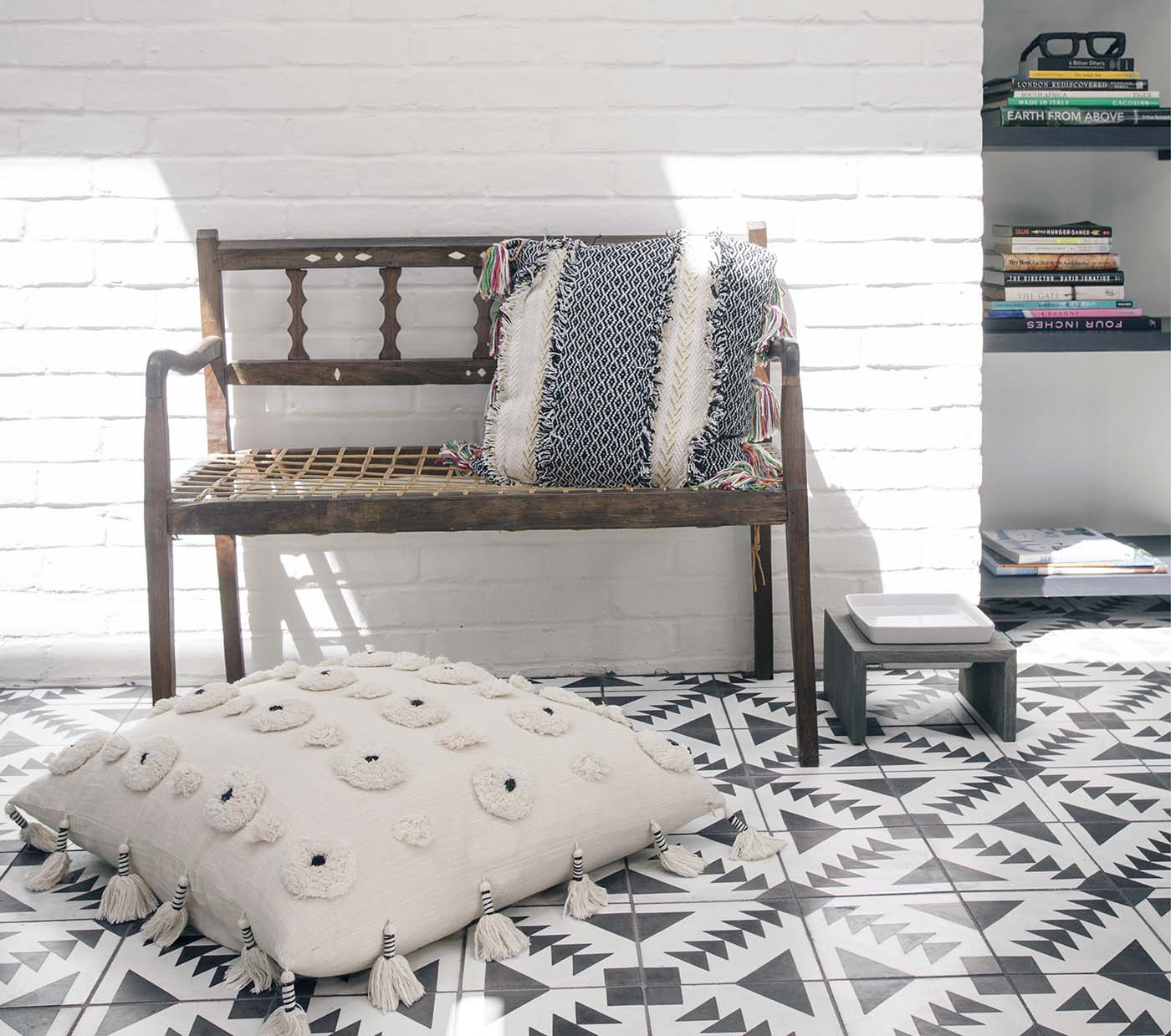 close up of black and white tiles, pillow and wooden chair
