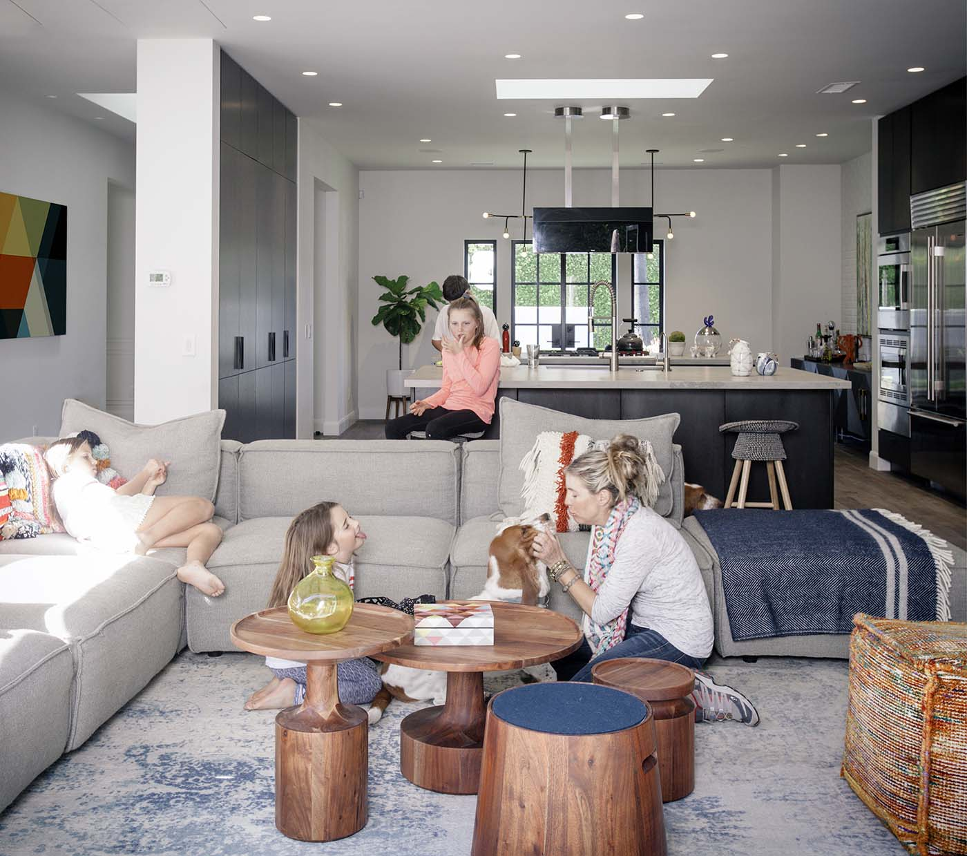 Living room with family and dog playing near bedside tables