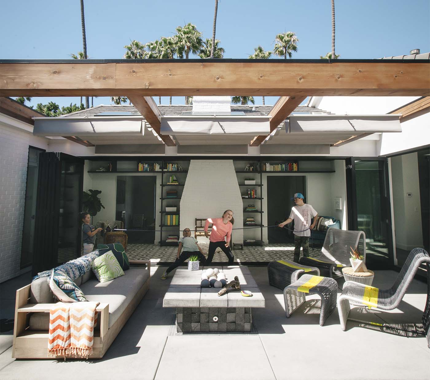 The outdoor area of a house in California with outdoor tables, chairs and children playing around