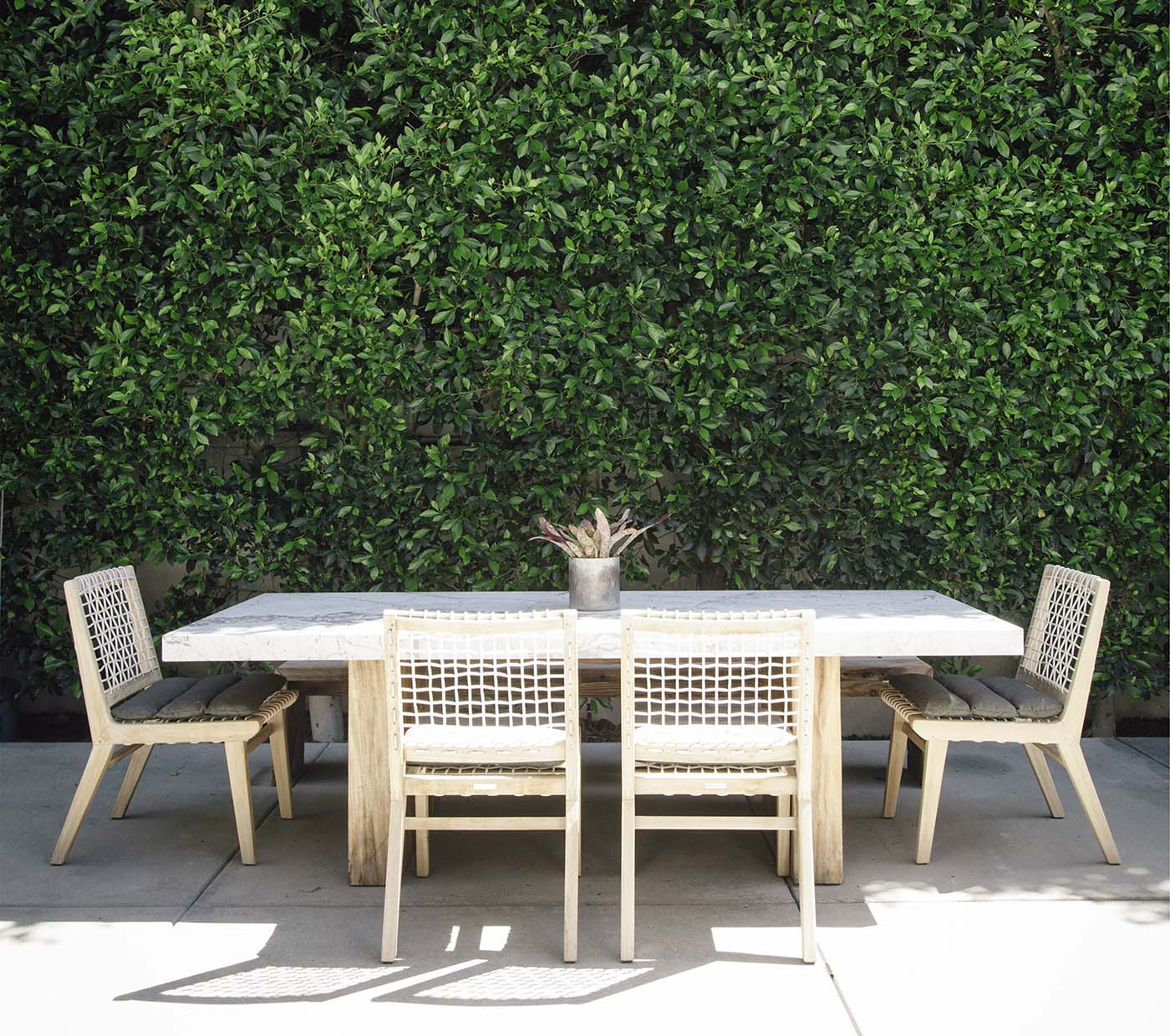 Close up of the outdoor area of a family house with a green grass wall and outdoor dining area